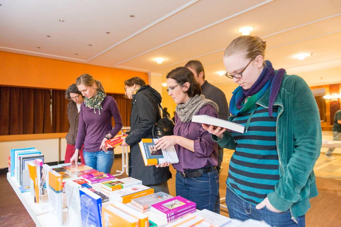Teilnehmer informieren sich bei einem Info-Stand der Buchhandlung Lehmann